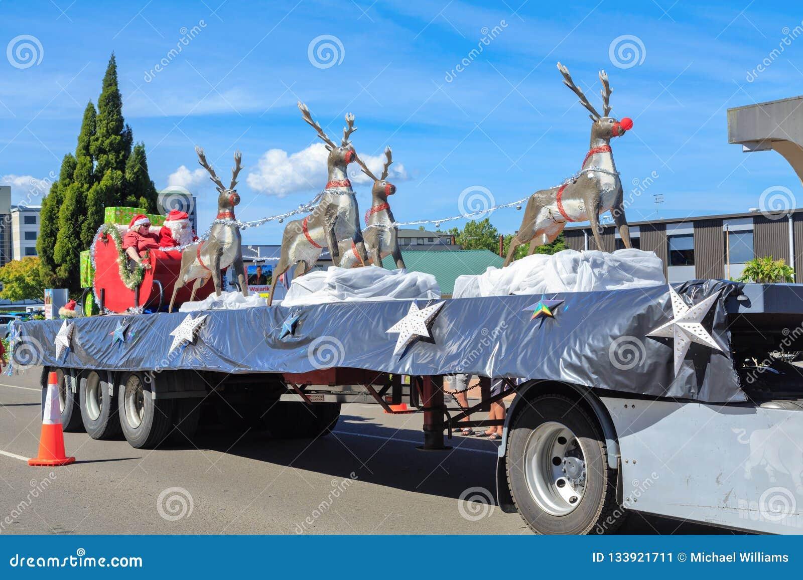Santa Claus en Mevr. Santa en hun rendier het berijden in Kerstmis paraderen vlotter