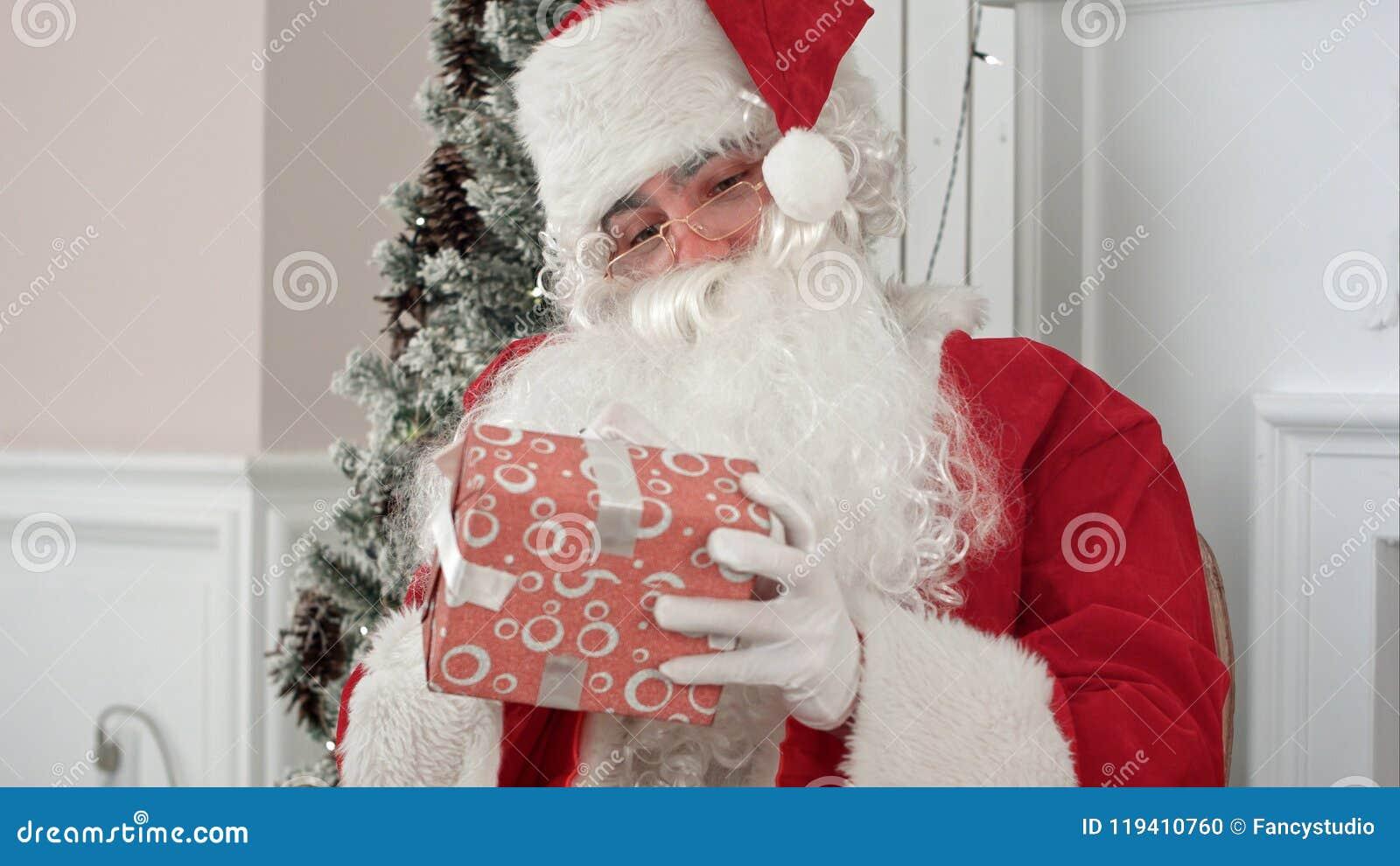 Santa Claus en sus presentes de firma del taller de la Navidad para los niños