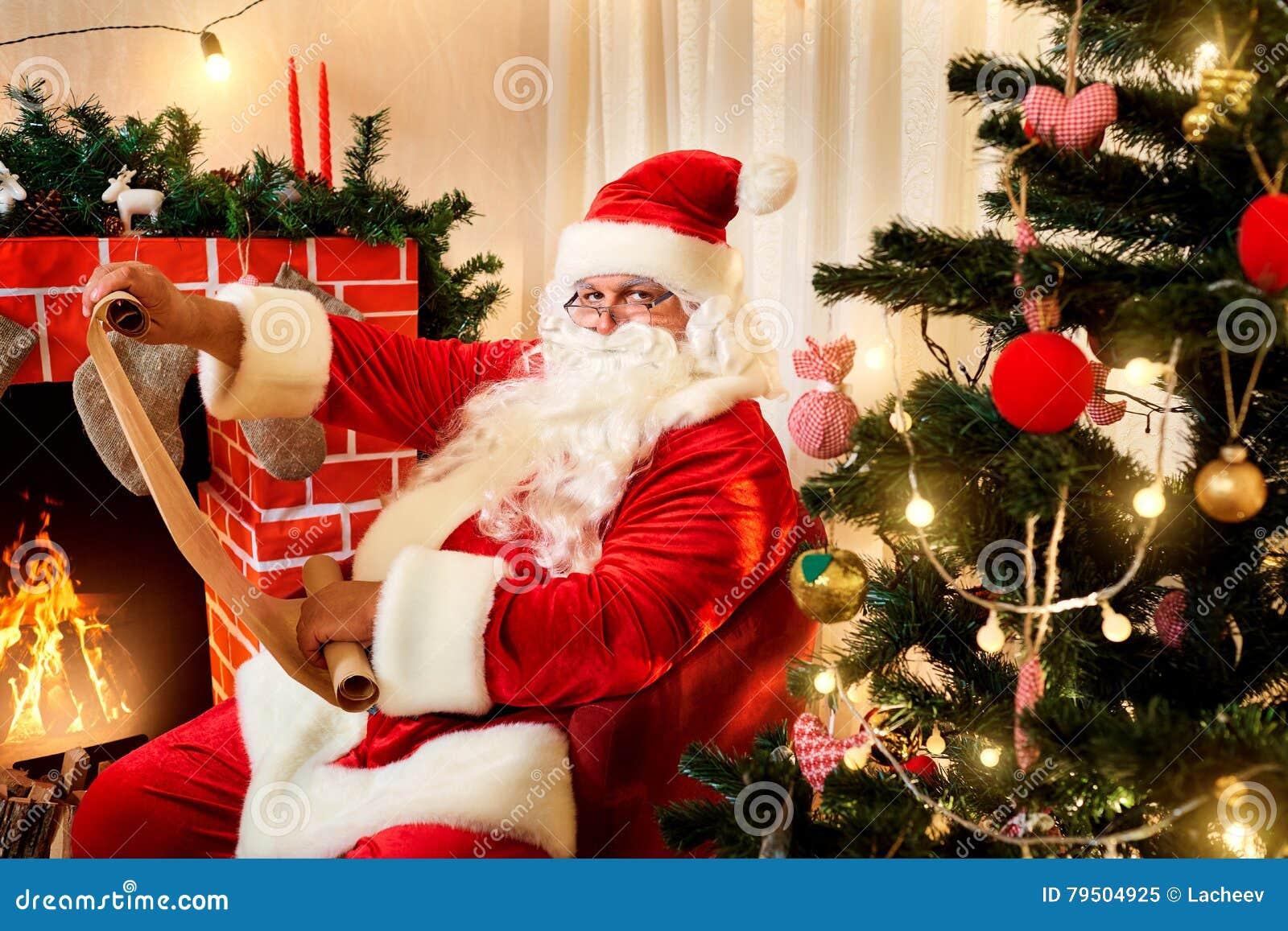 Santa Claus en una lista de la Navidad con un regalo en las manos del