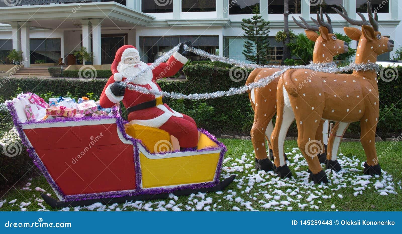 Santa Claus entrega los regalos en un trineo dibujado por el reno, escultura decorativa del jardín, la Navidad del verano