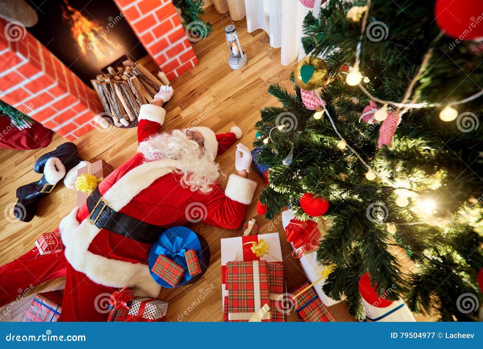 Santa Claus está durmiendo, cansado, bebida en un cuarto cerca del firepla