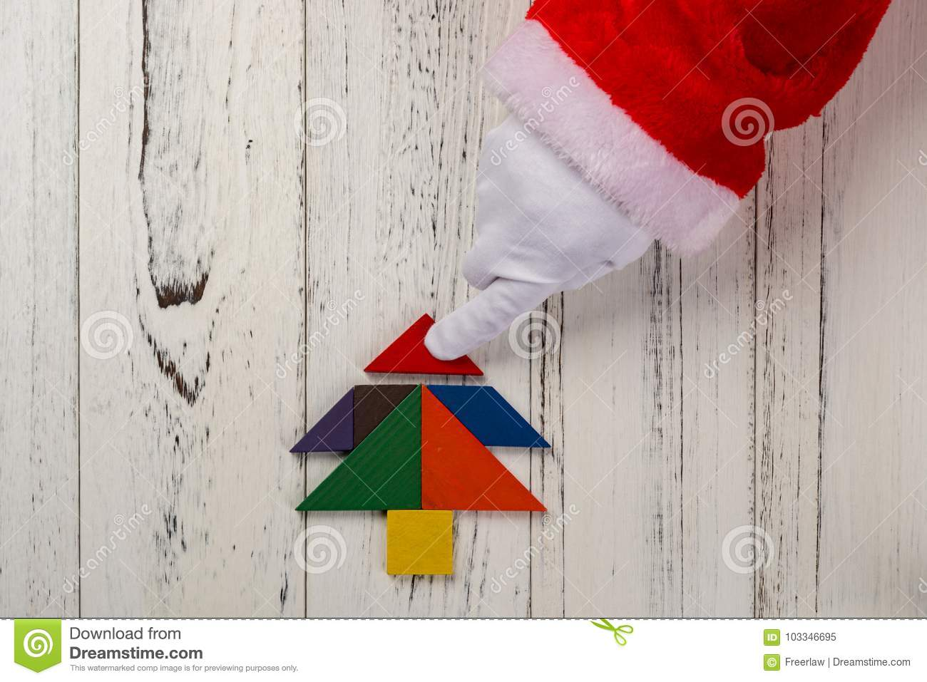 santa claus finishing the last bit of christmas tree made by tangram