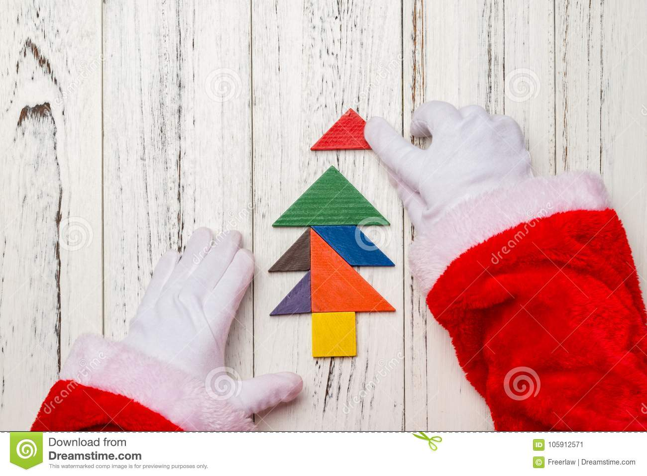 santa claus finishing the last bit of christmas tree made by wooden tangram