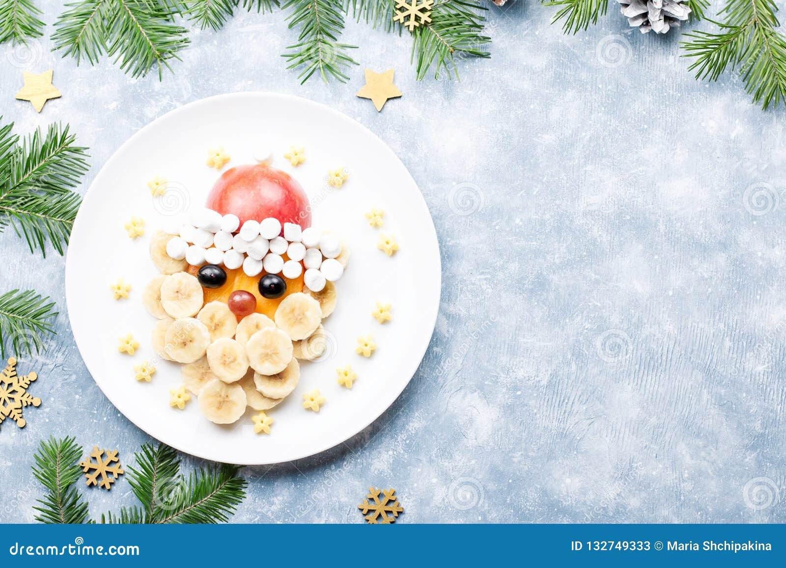 Santa Claus-gezicht van vruchten en heemst op een plaat wordt gemaakt die Kerstmisvoedsel voor kinderen Hoogste mening
