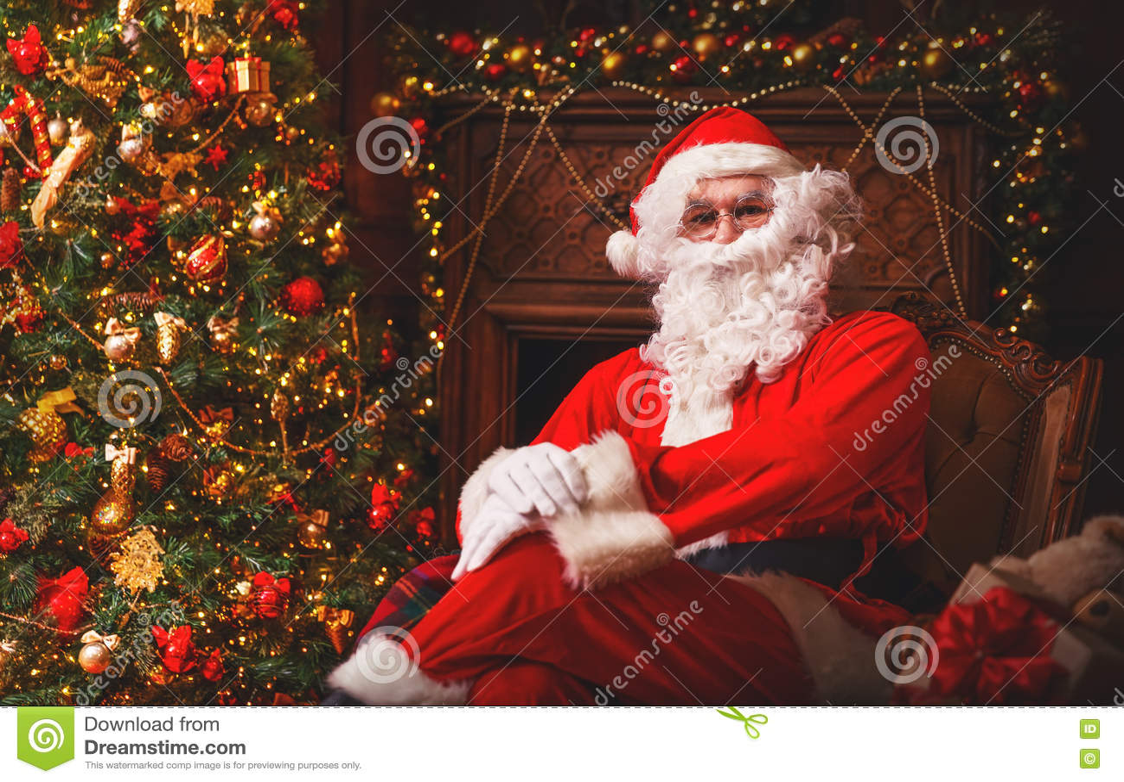 Santa claus with gifts around christmas tree stock photo