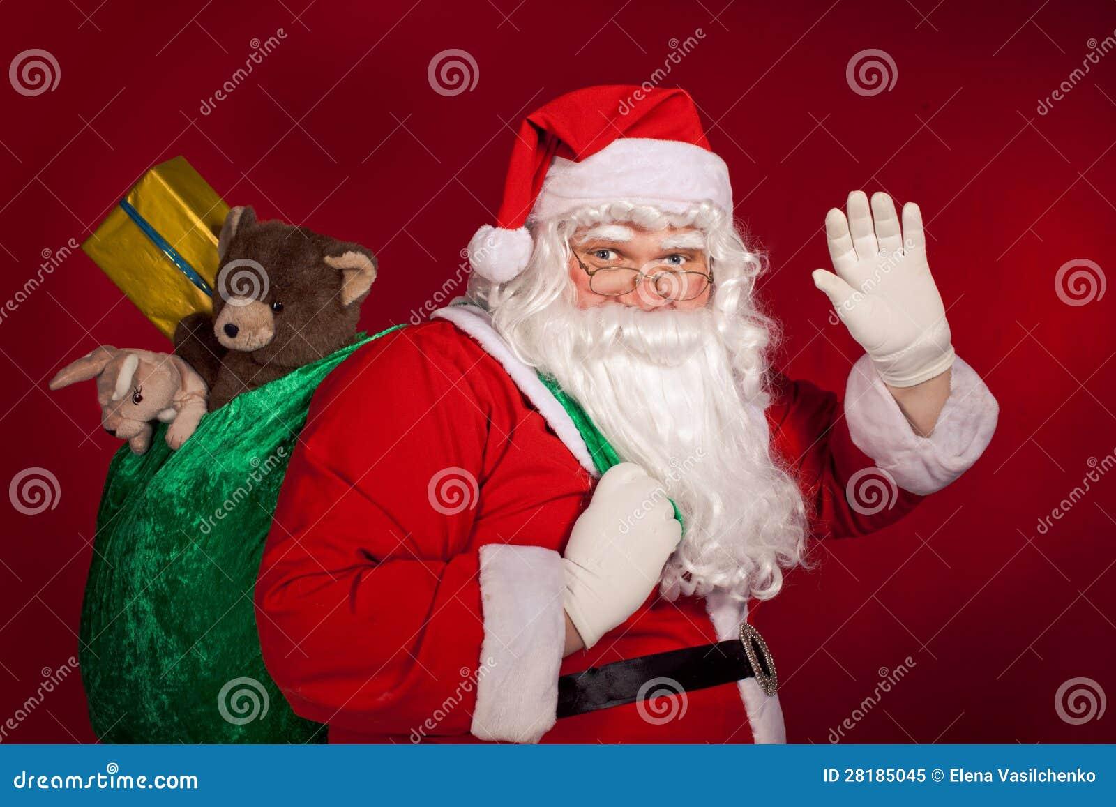 Santa Claus Greeting And Holding His Bag Royalty Free