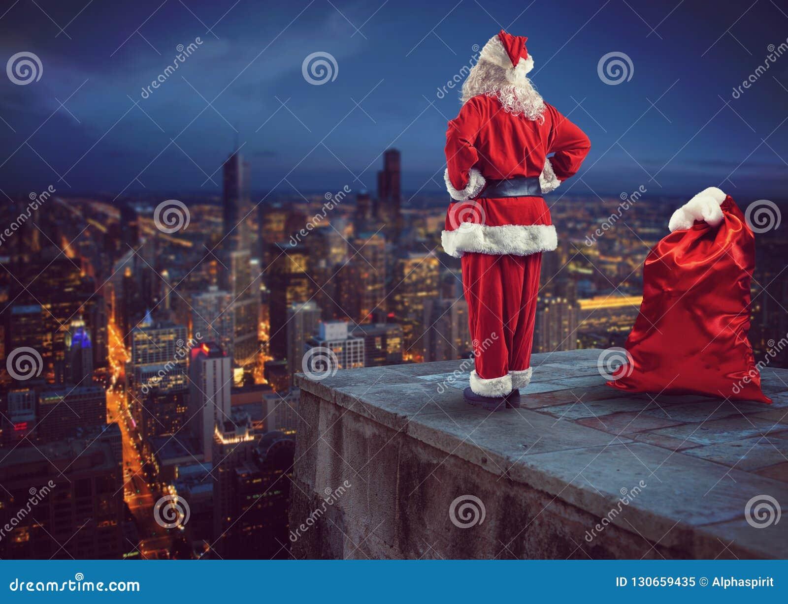 Santa Claus guarda dall alto in basso la città che aspetta per consegnare i presente