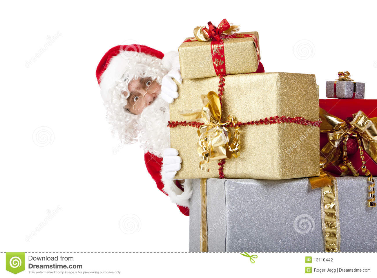 Santa claus hiding behind christmas gift boxes stock