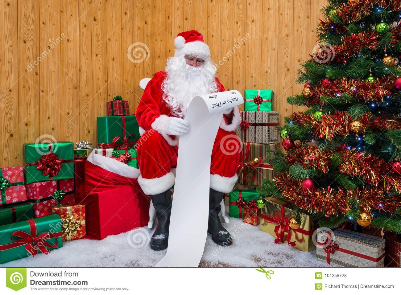 Santa Claus in a grotto checking the naughty or nice list