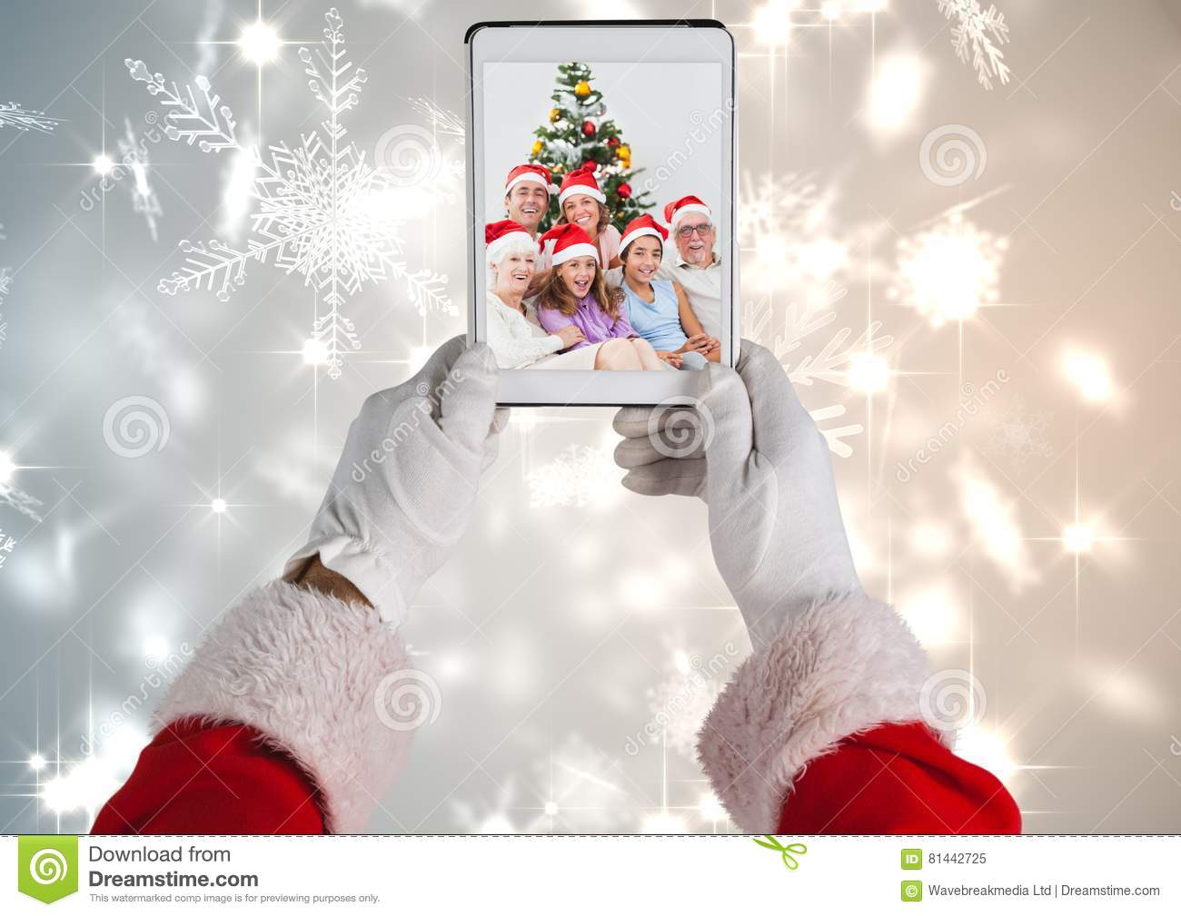 Santa claus holding a digital tablet with photo of christmas family