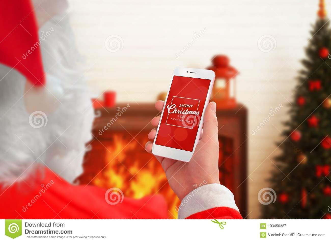 Santa Claus Holding Mobile Phone With Christmas Greeting On Display