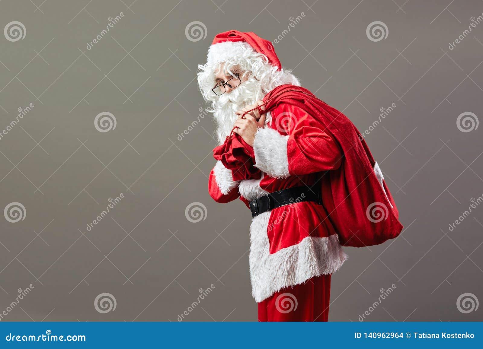 Santa Claus i exponeringsglasställningar med påsen med julgåvor på hans baksida på den gråa bakgrunden