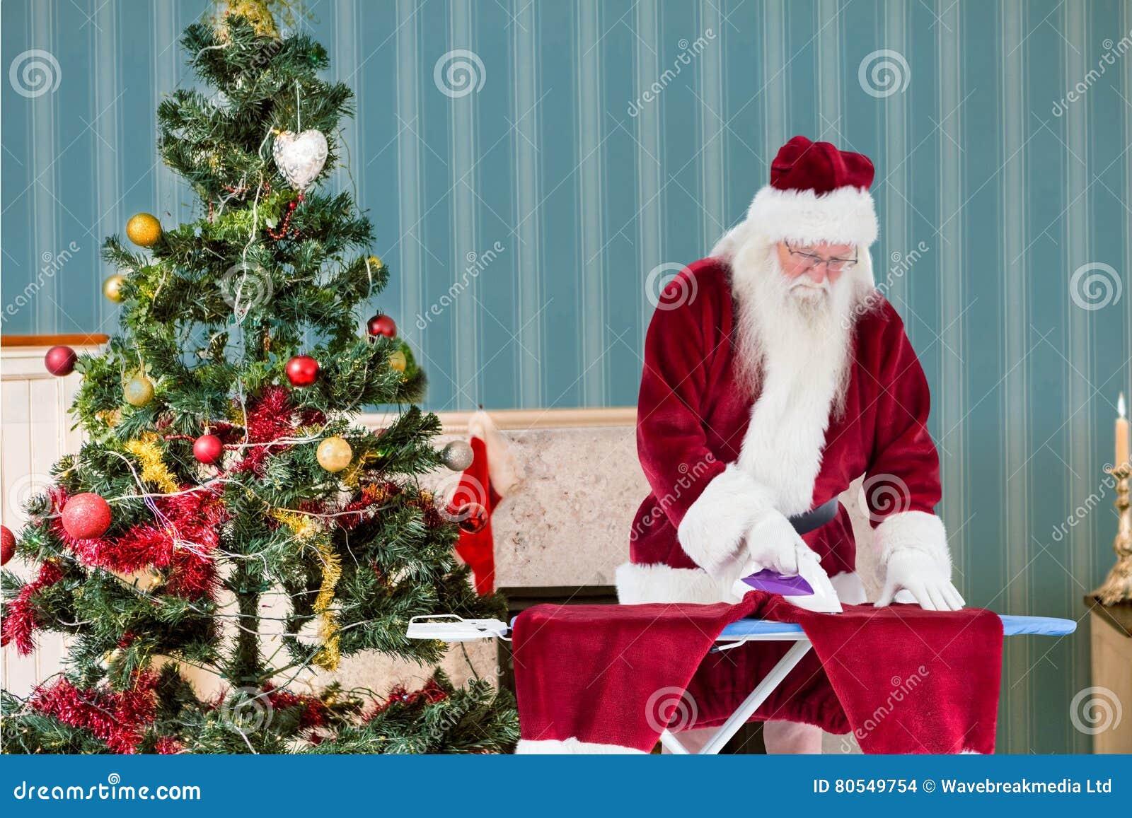 Santa claus ironing his clothes