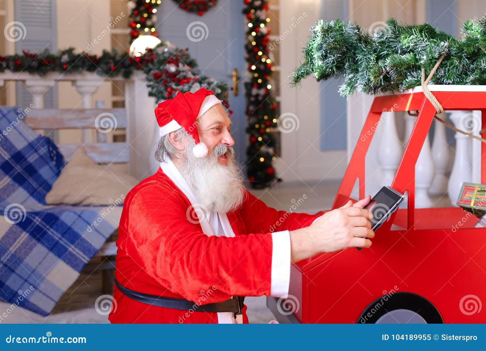 Santa Claus joyeuse appréciant avec l instrument moderne