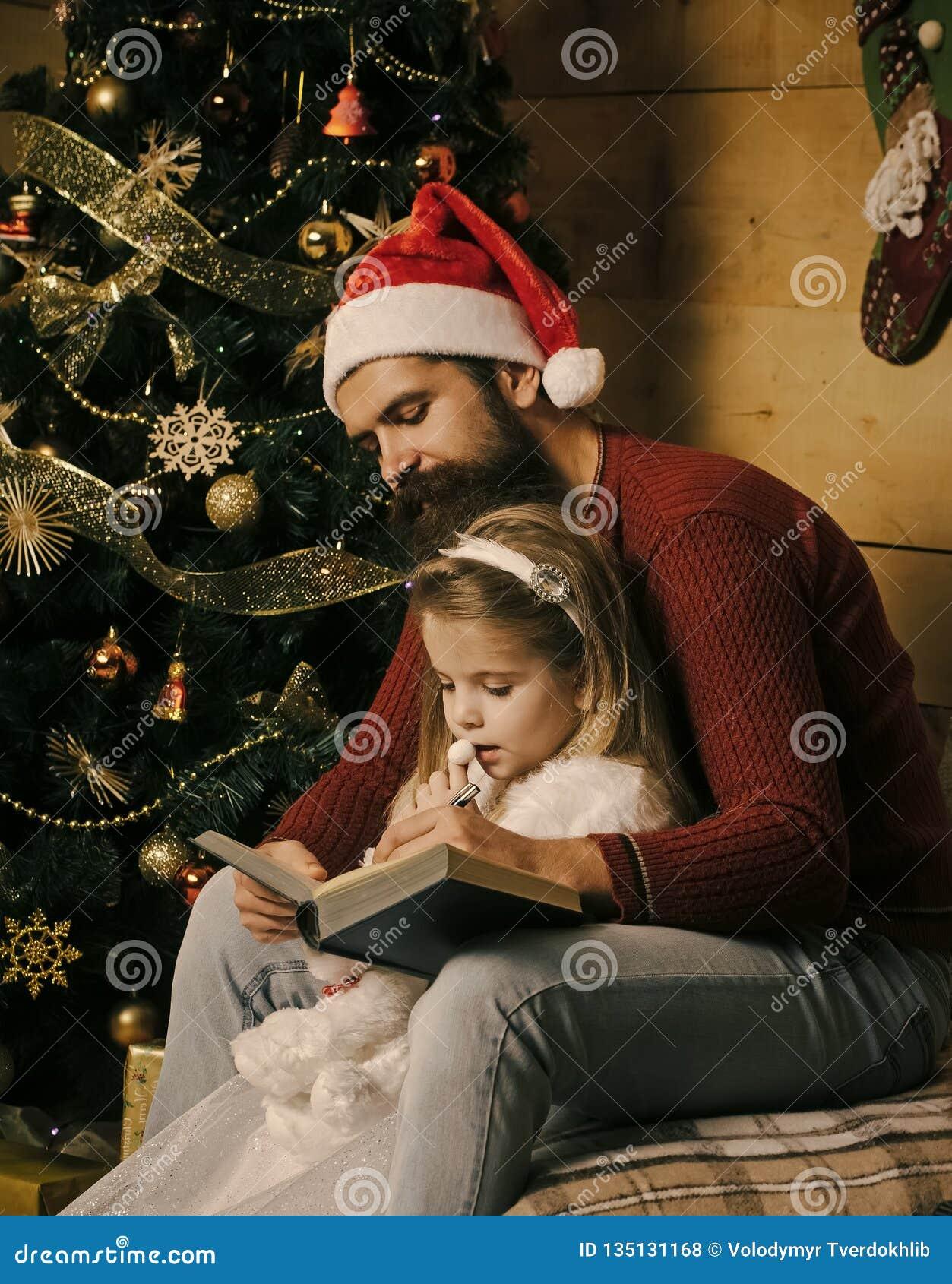 Santa claus kid and bearded man at Christmas tree.