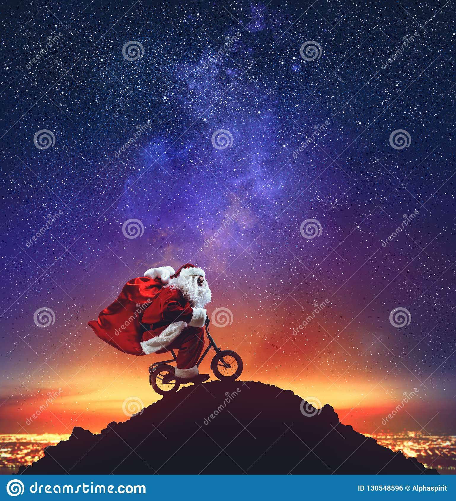 Santa Claus on a little bike on the peak of a mountain under the stars