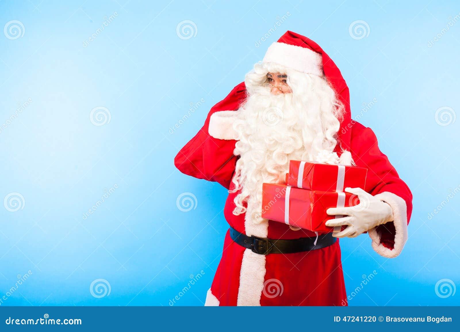 Santa Claus med gåvor på händer på blå bakgrund