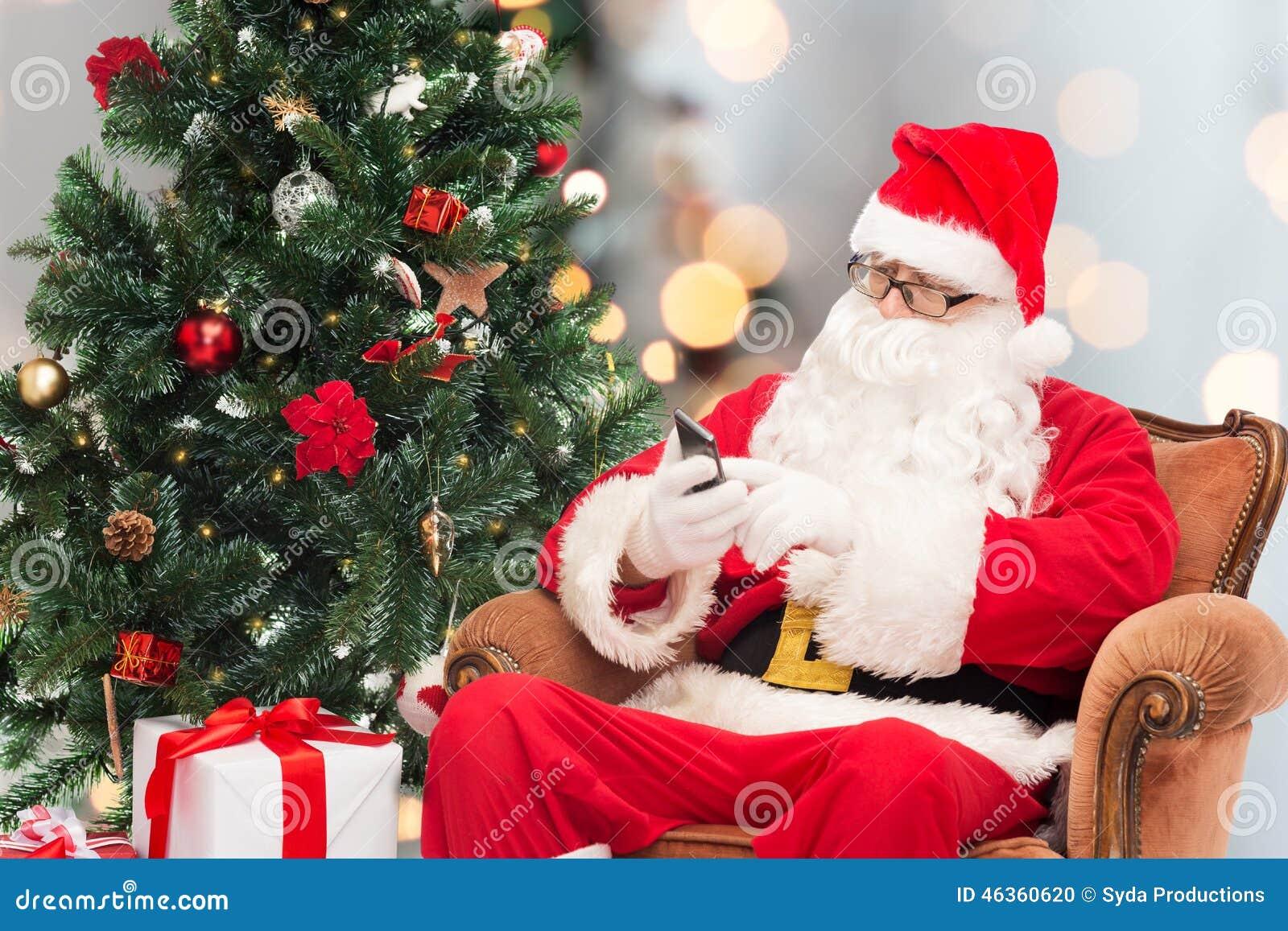 Santa Claus med smartphonen och julträdet