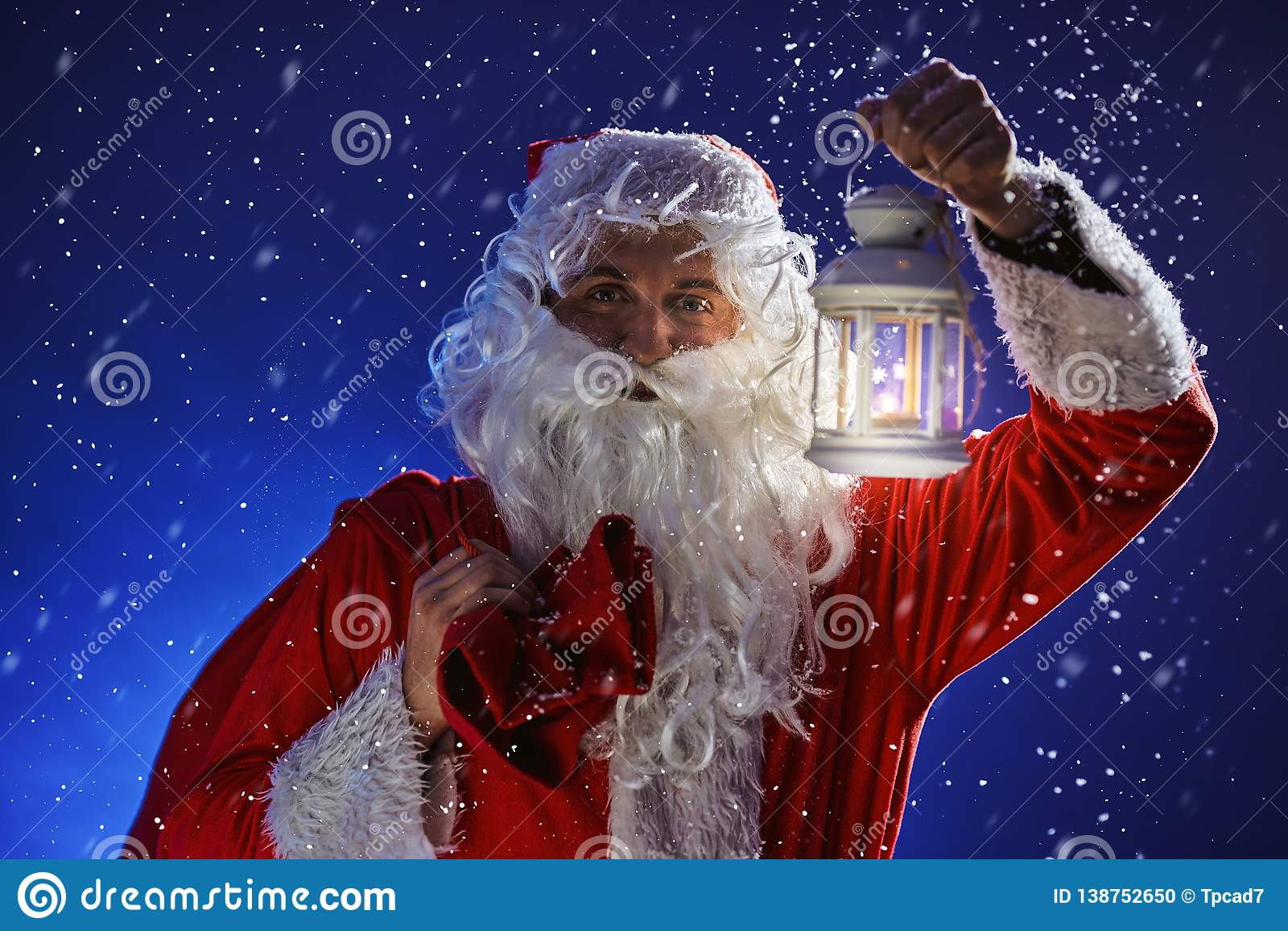 Santa Claus mit einem langen weißen Bart hält Kerzenhalter mit brennender Kerze gegen einen schneienden blauen Himmel Weihnachten