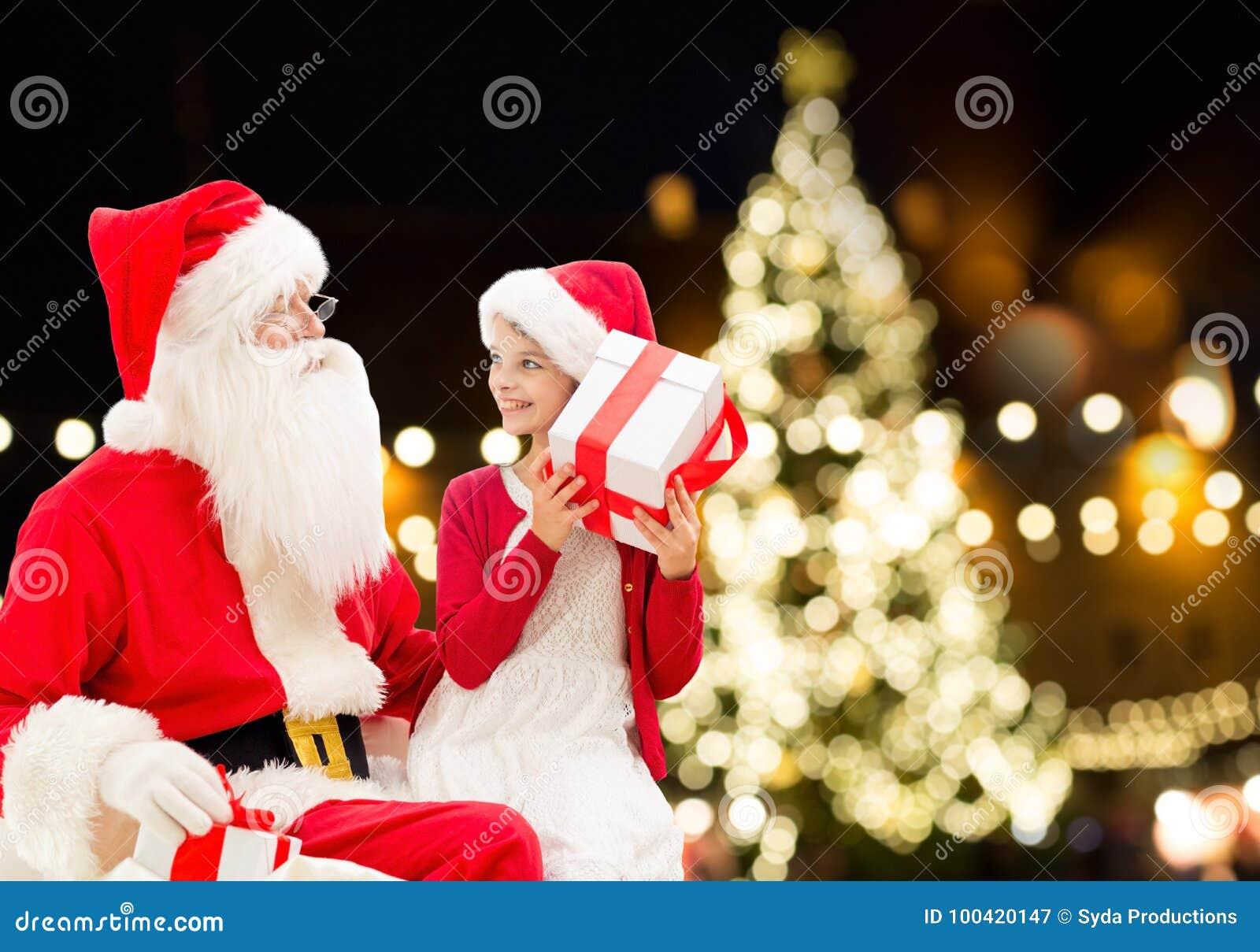 Santa Claus och lycklig flicka med julgåvan