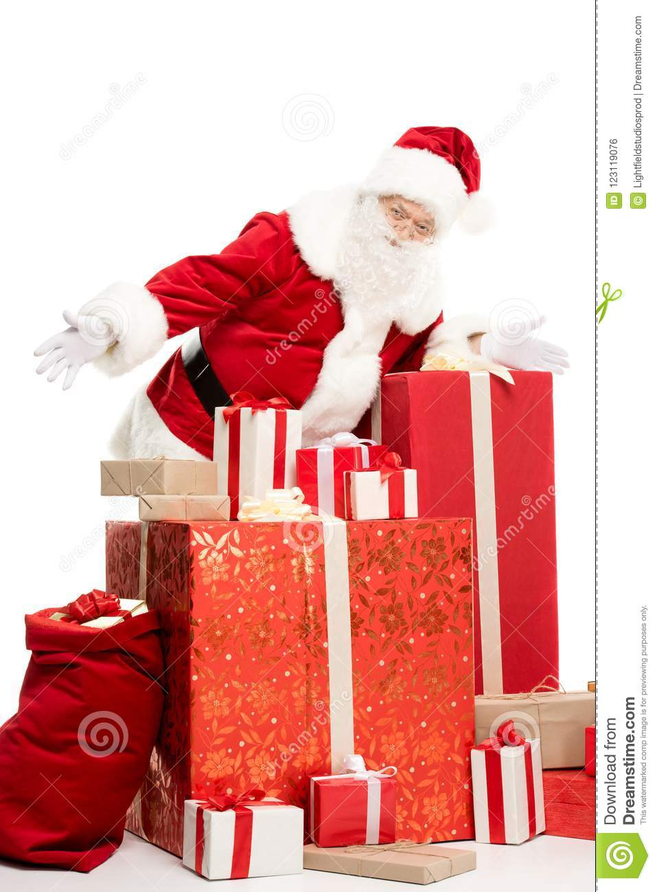 Happy Santa Claus Standing With A Pile Of Christmas Gifts On White