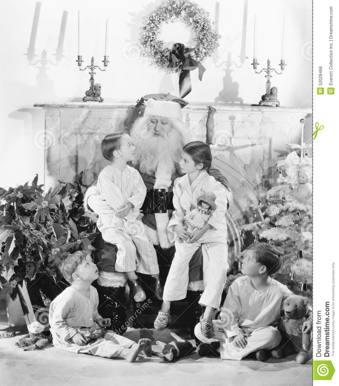 Santa Claus with presents and a group of children in front of a fire place