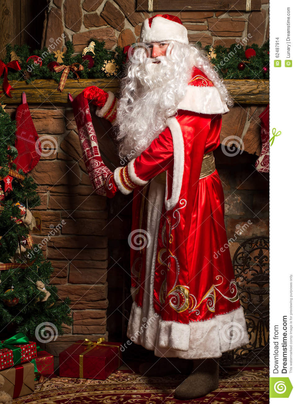 Santa Claus Putting Gifts In Christmas Stockings At ...