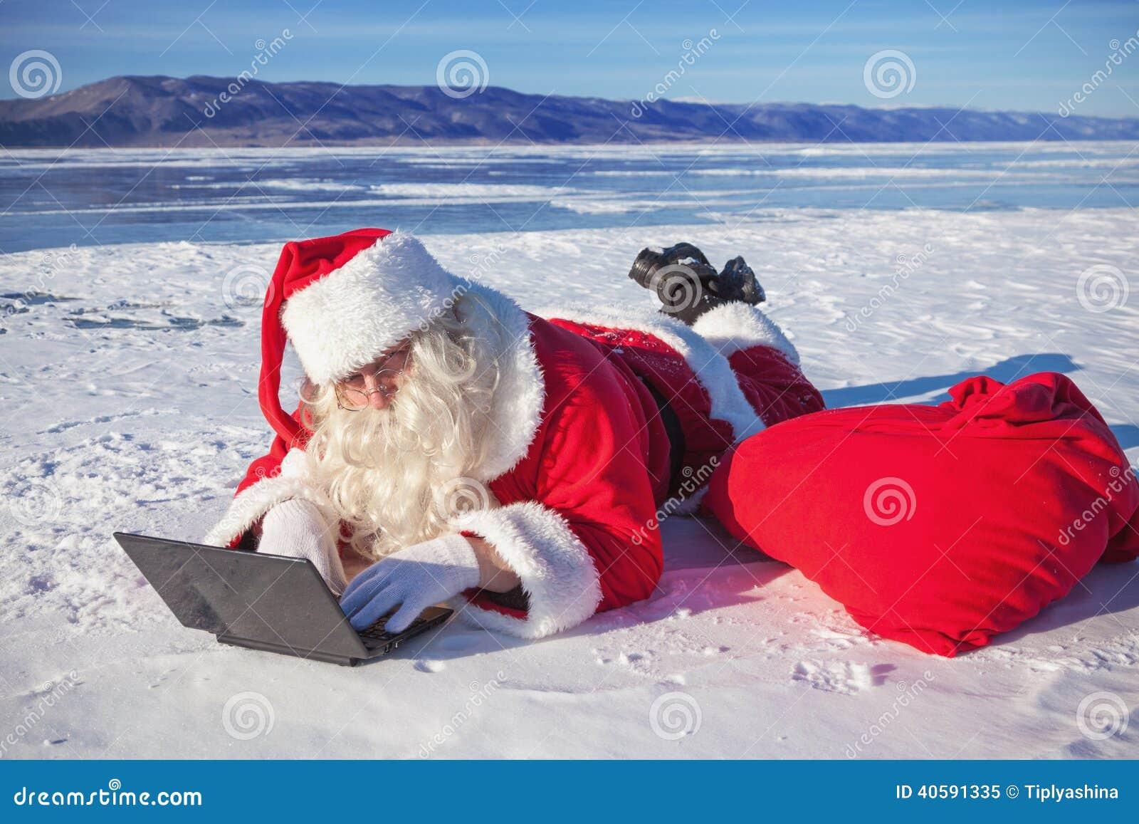 Santa Claus que encontra-se na neve, olhando a notícia do portátil