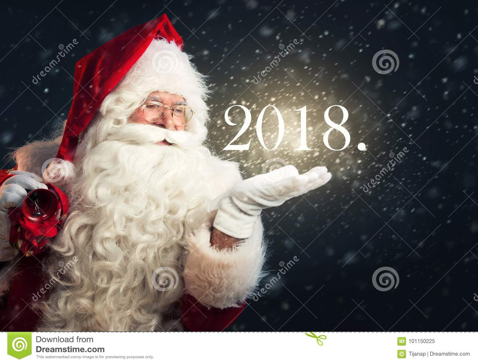 Santa Claus que funde a neve mágica de sua mão, guardando um ano 2018