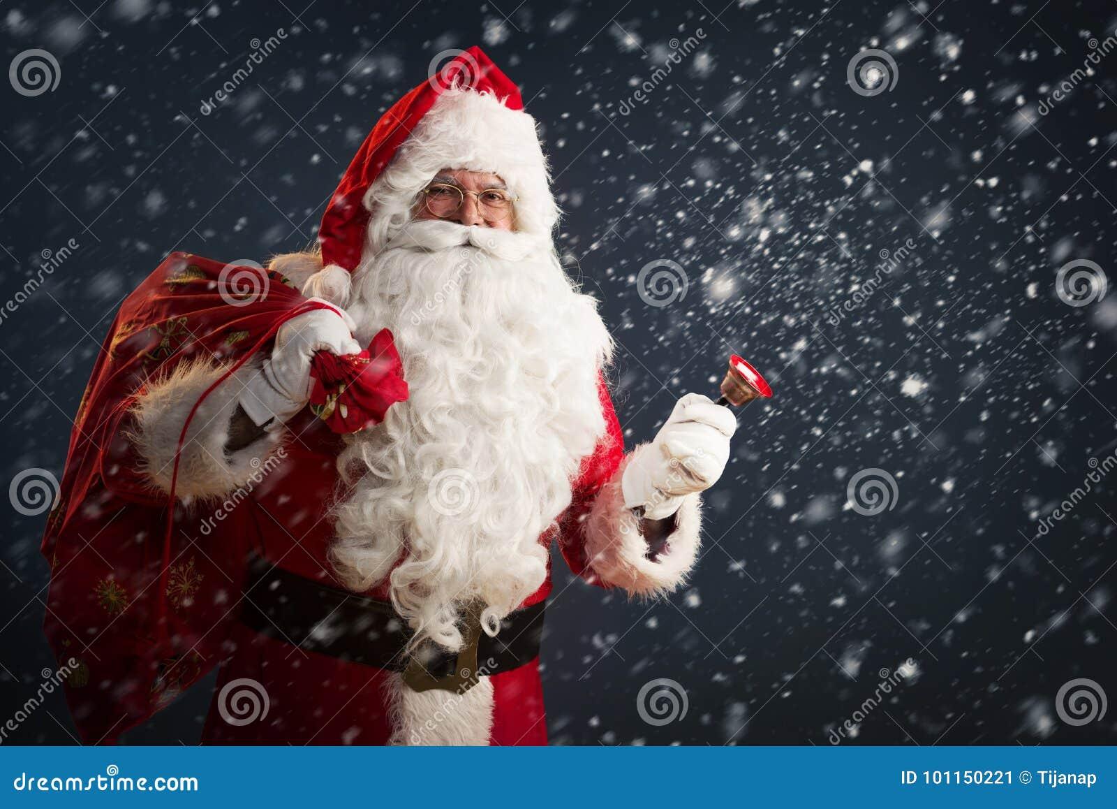 Santa Claus que guarda um saco com presentes e que soa um sino em um fundo escuro