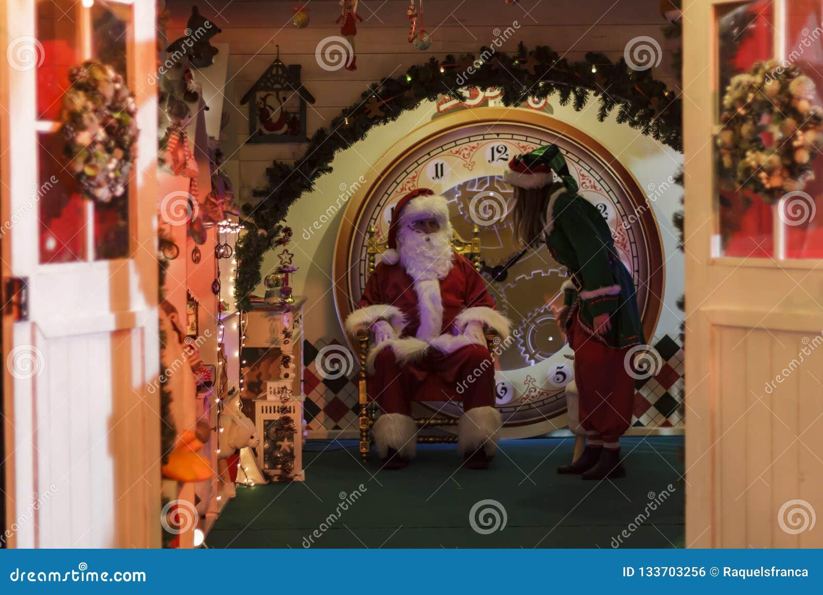 Santa Claus que senta-se em seu duende da poltrona e do ajudante