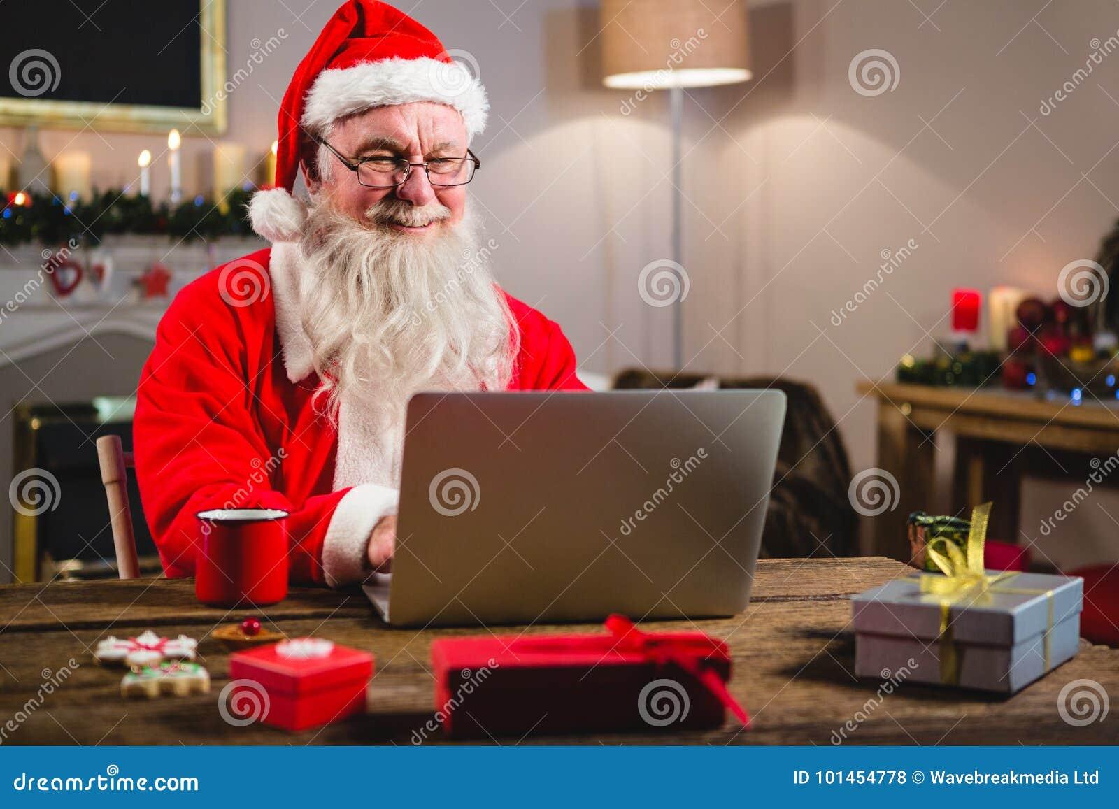 Santa Claus que usa o portátil na tabela