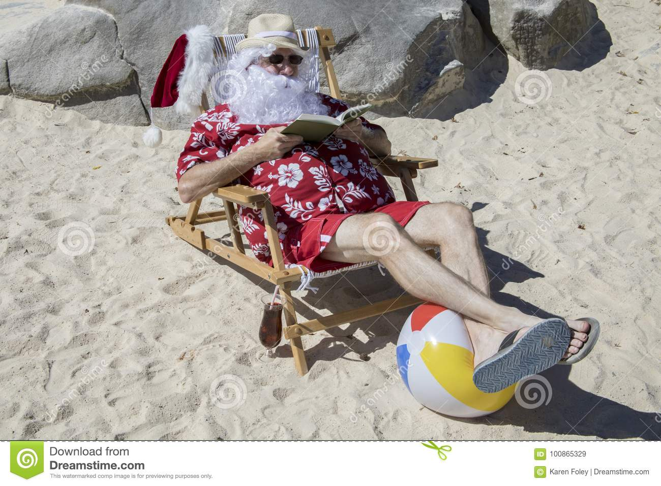 111f0d3f Santa Claus in red swimming trunks ans Hawaiian shirt lounging on sandy  beach with straw hat and sunglasses reading book with tropical drink.