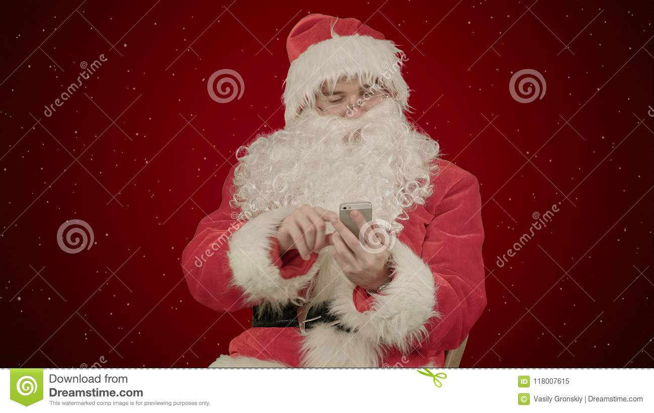 santa claus reads and sends text messages from his cell phone on red background with snow