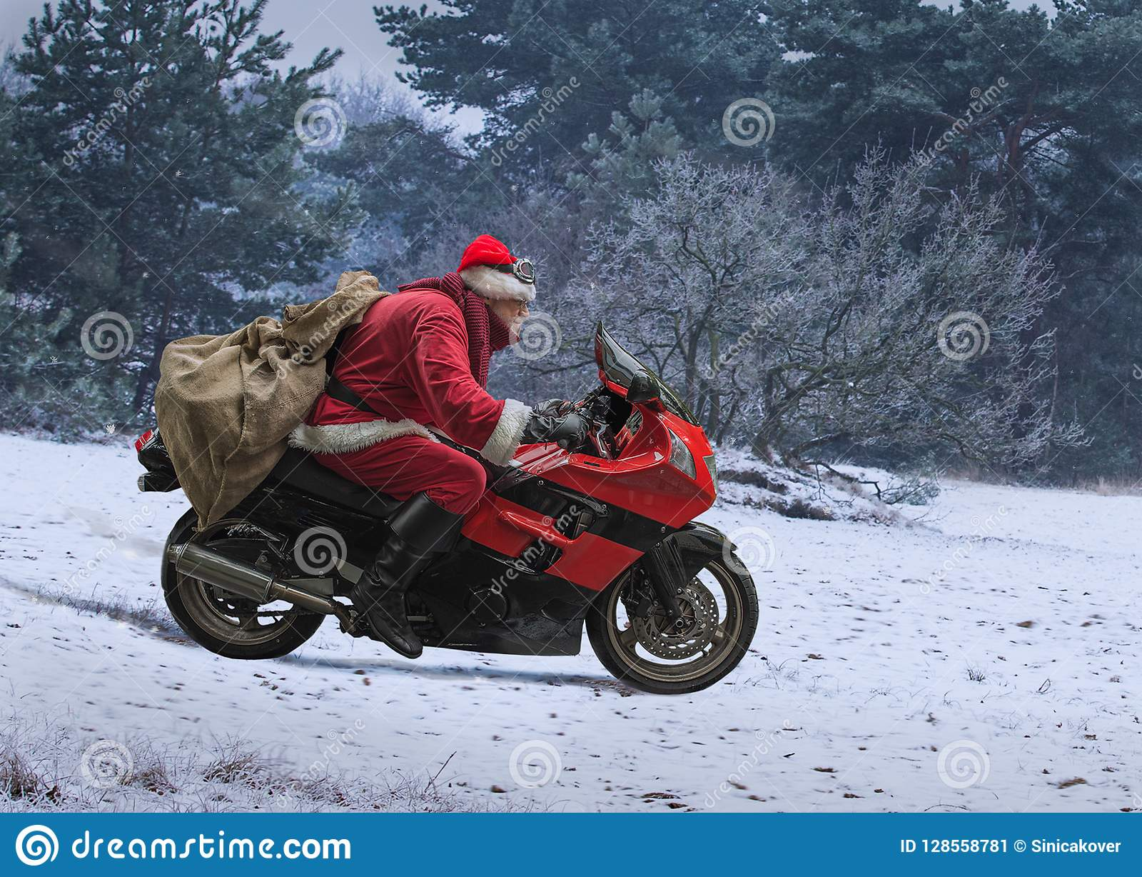 Santa Claus on red motorcycle with a sack driving along winter s