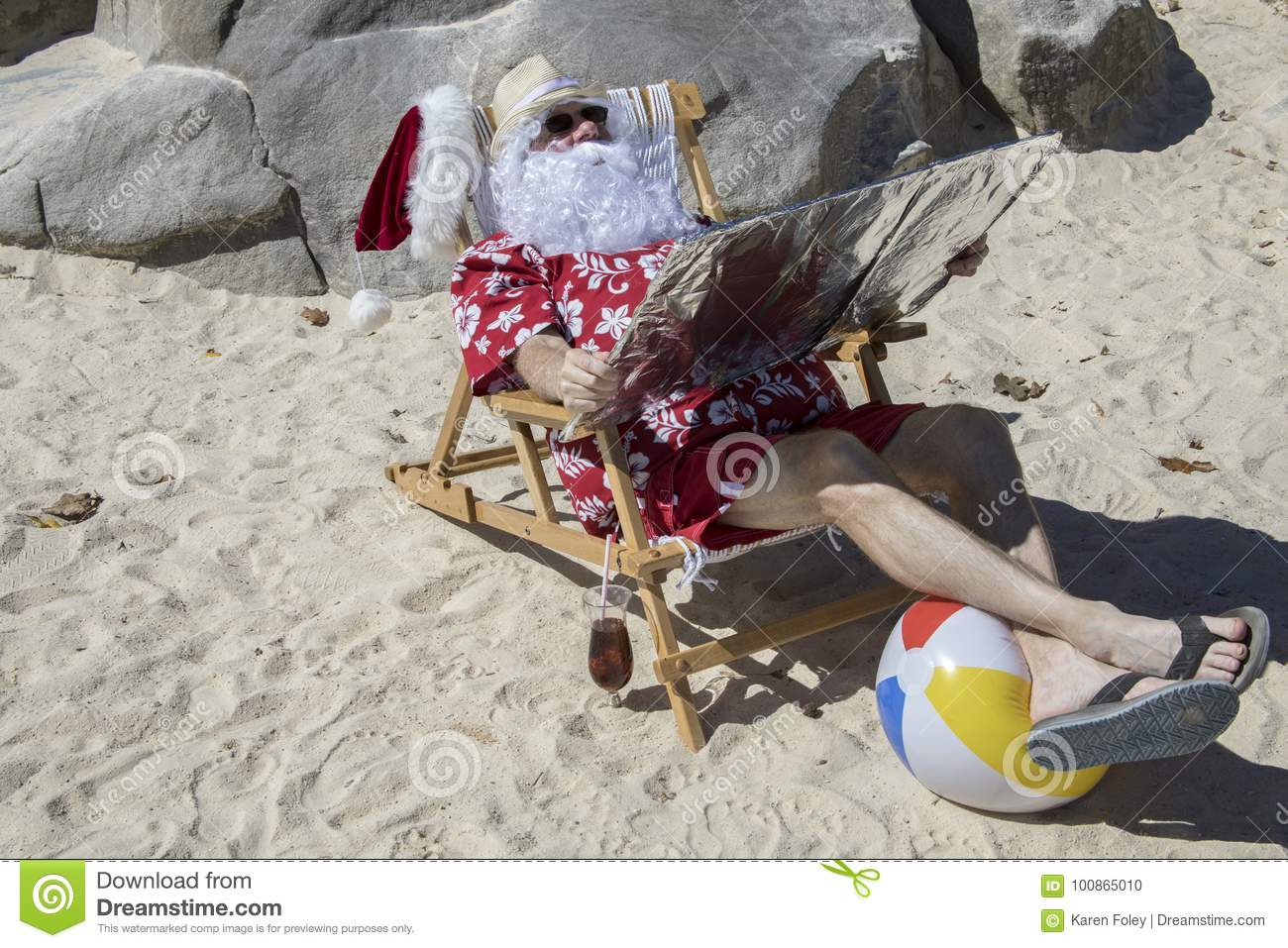cac29553 Santa Claus in red swimming trunks ans Hawaiian shirt lounging on sandy  beach with straw hat and sunglasses using reflector to tan.
