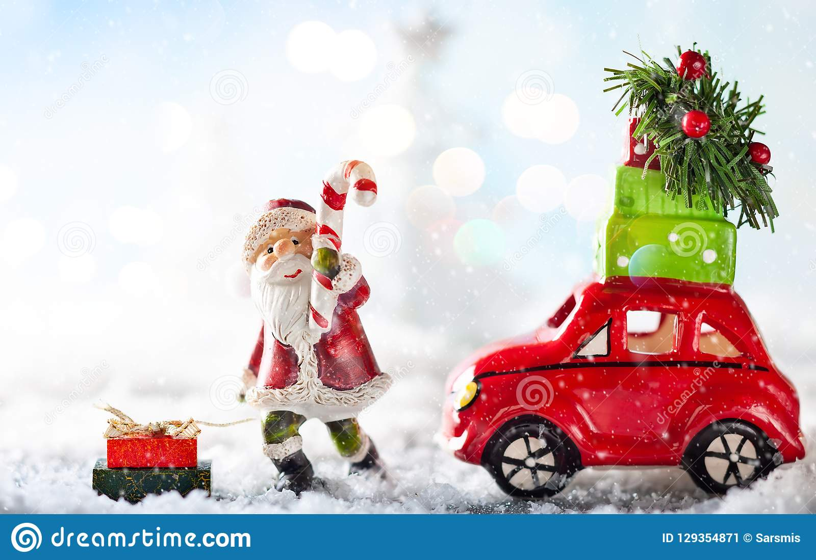 Santa Claus and red toy car carrying Christmas gifts in snowy la
