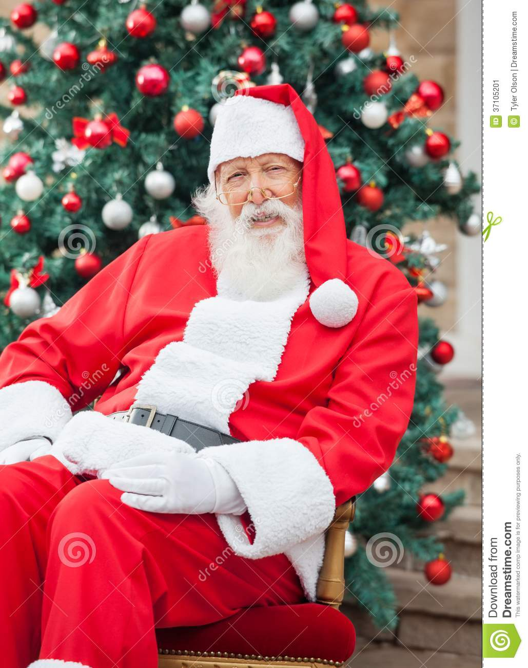 Santa Claus Sitting Against Decorated Christmas