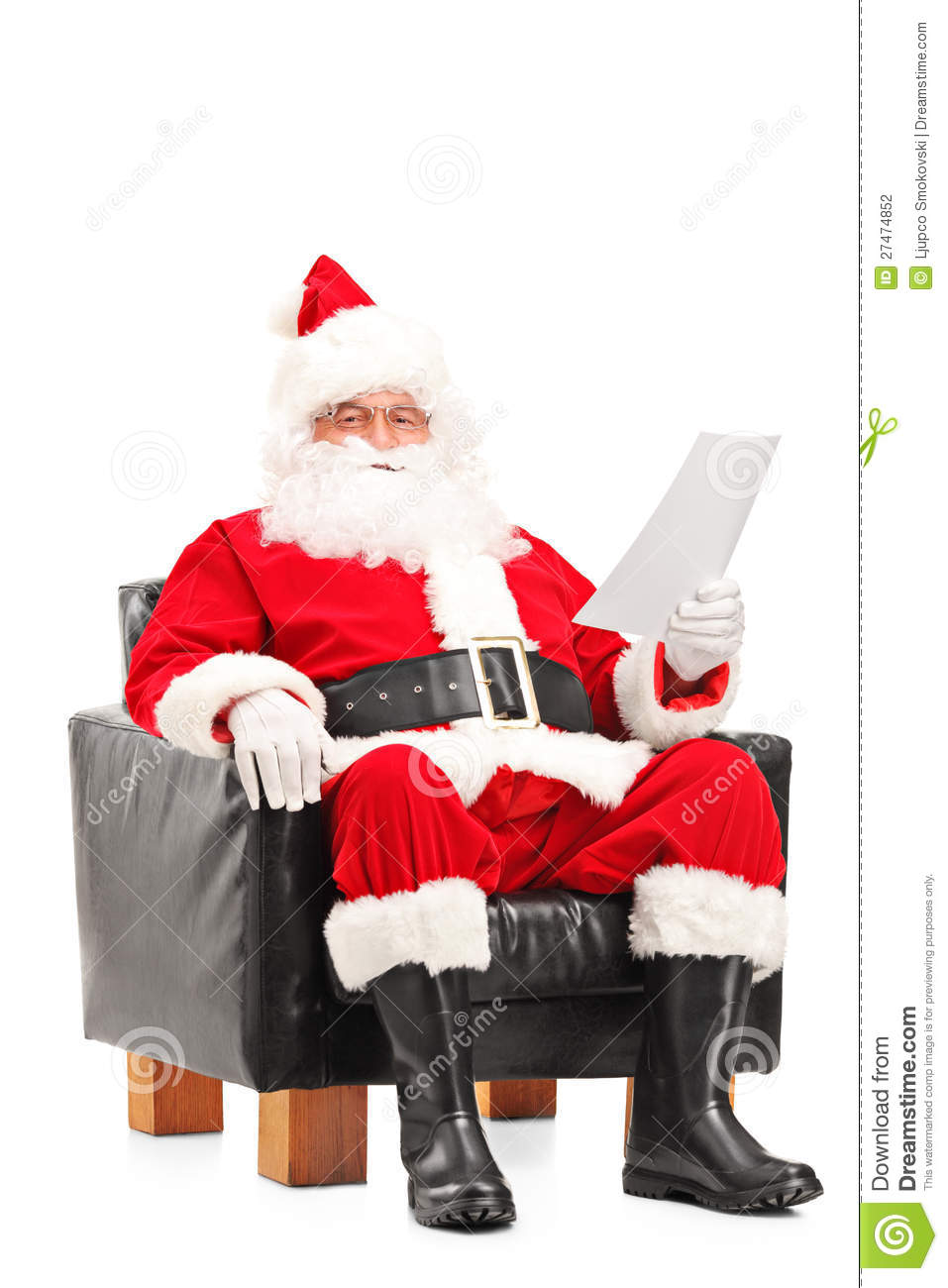 Santa Claus sitting in a comfortable armchair and reading a letter on ...