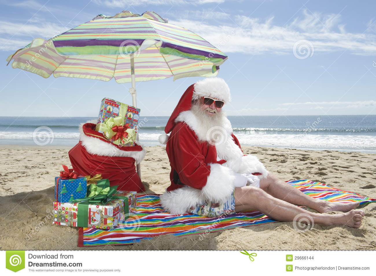 Santa claus sitting under parasol with gifts on beach stock photo santa claus sitting under parasol with gifts on beach jeuxipadfo Choice Image