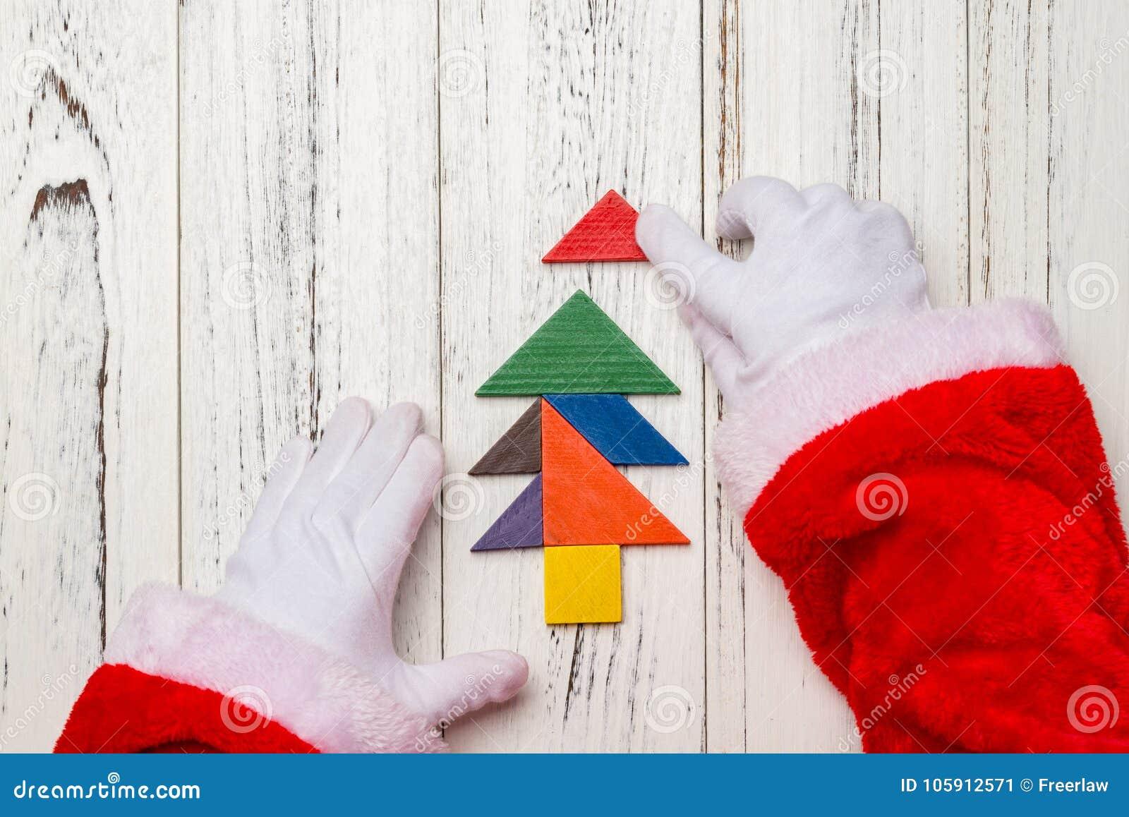 Santa Claus som avslutar den sista biten av julgranen som göras av den wood tangramen