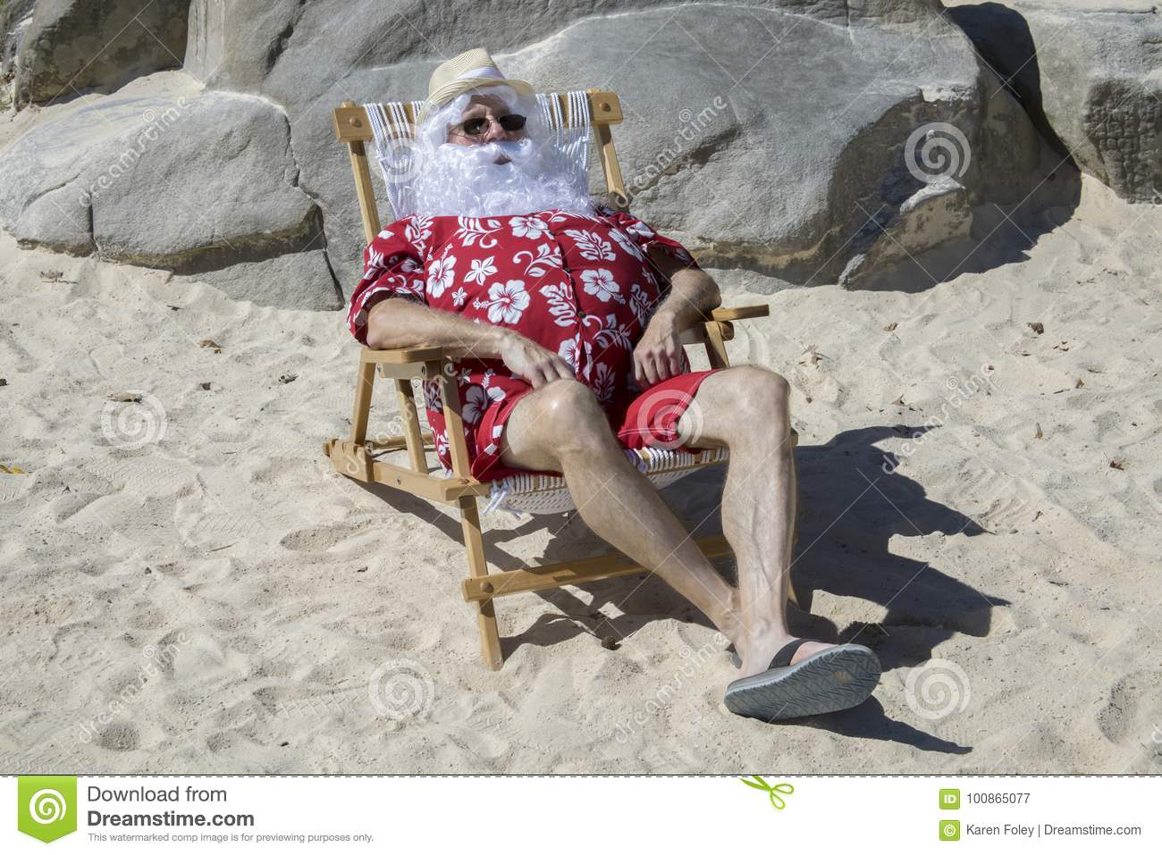 56c916f4 Santa Claus in red swimming trunks ans Hawaiian shirt lounging on sandy  beach with straw hat and sunglasses.