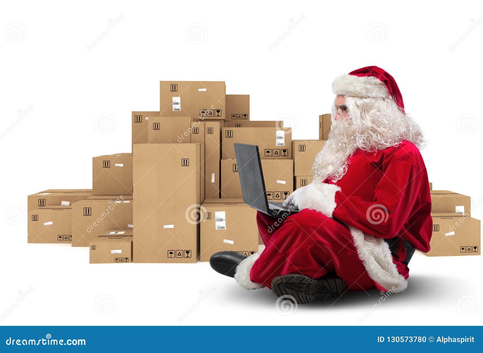 Santa Claus tecnologico que senta-se com portátil compra presentes do Natal com comércio eletrônico