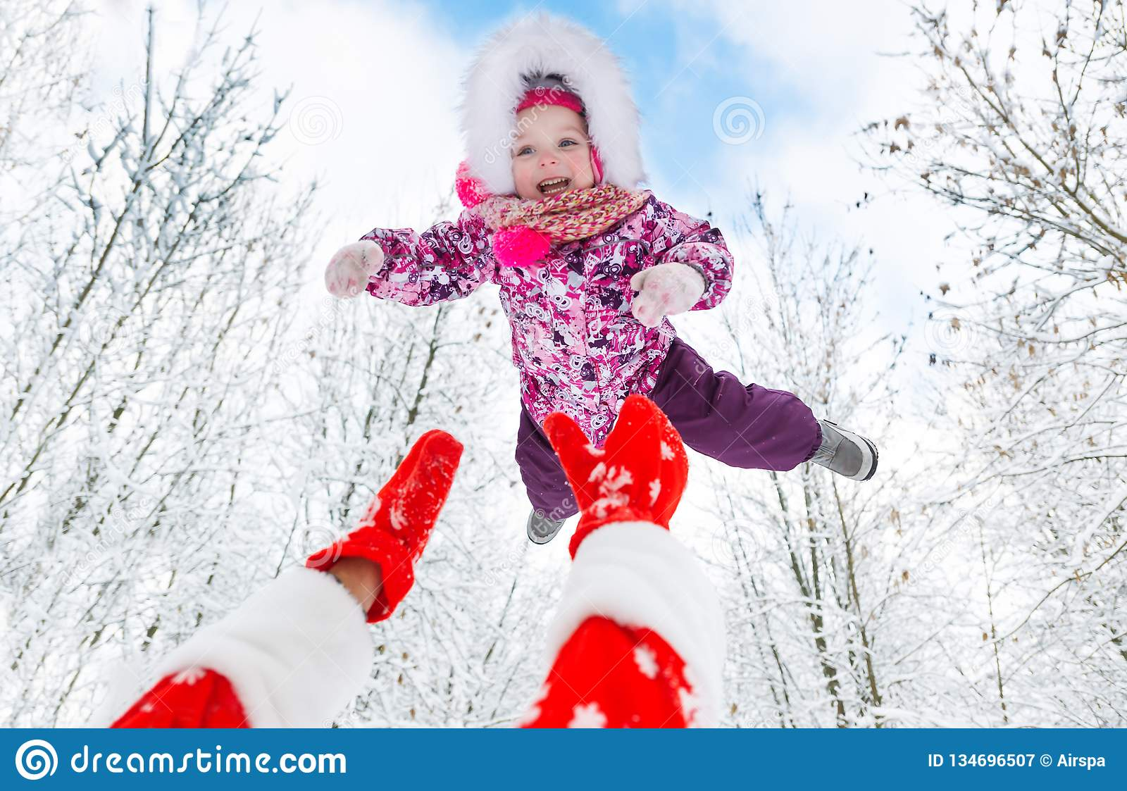 Santa Claus throws up overhead cute little girl in winter forest on Christmas
