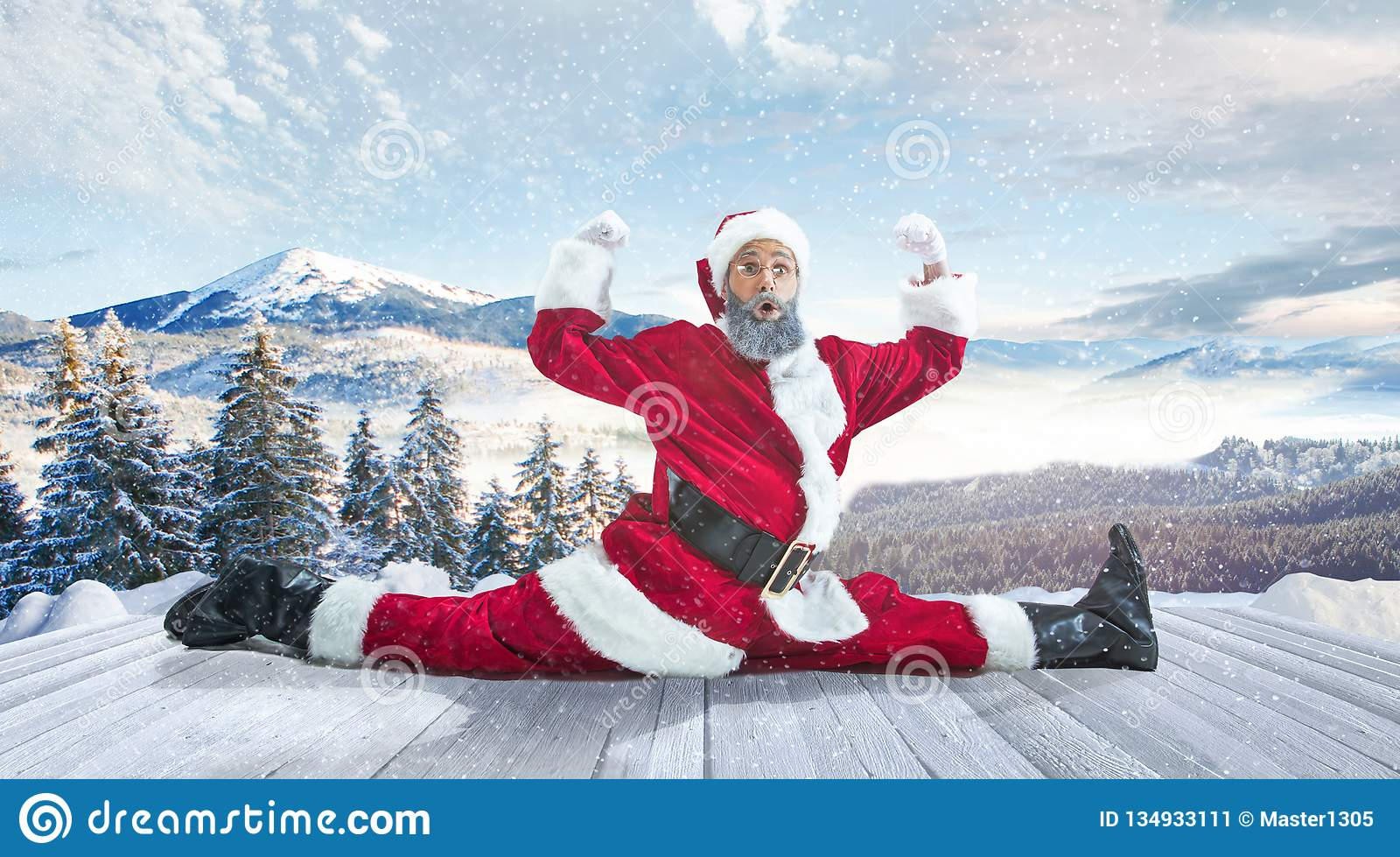 Santa Claus with traditional red white costume in front of white snow winter landscape panorama