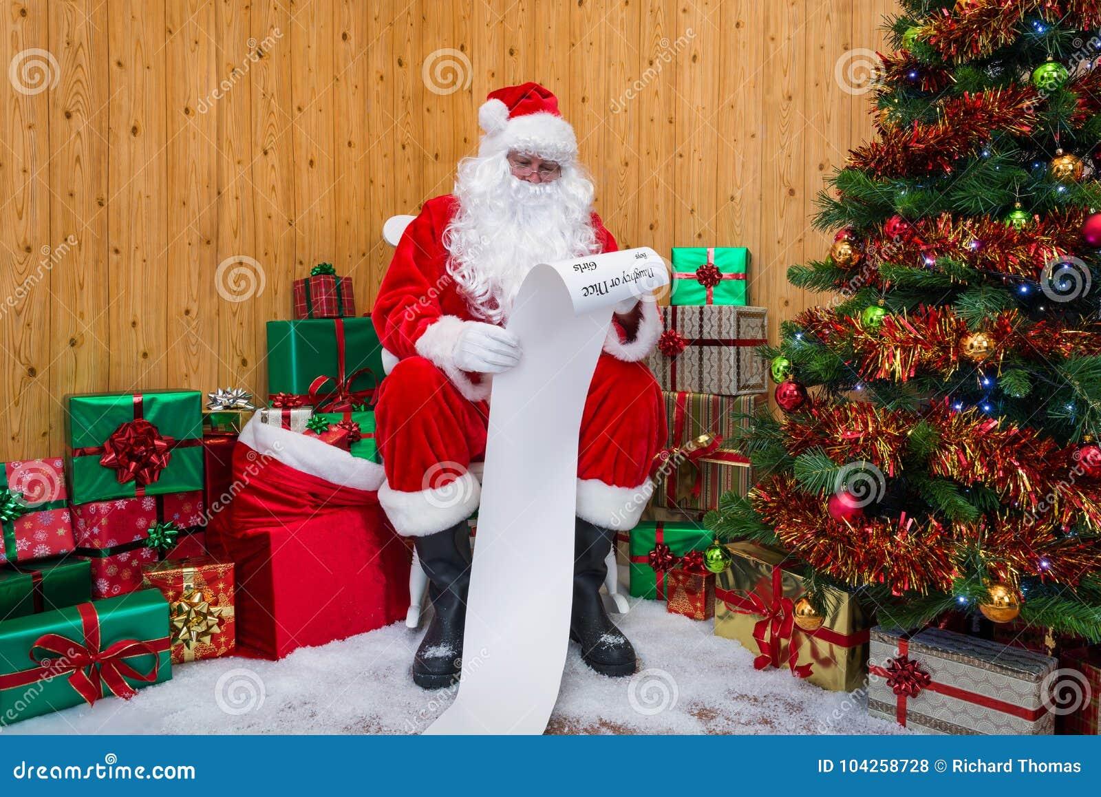 Santa Claus in una grotta che controlla la lista impertinente o piacevole