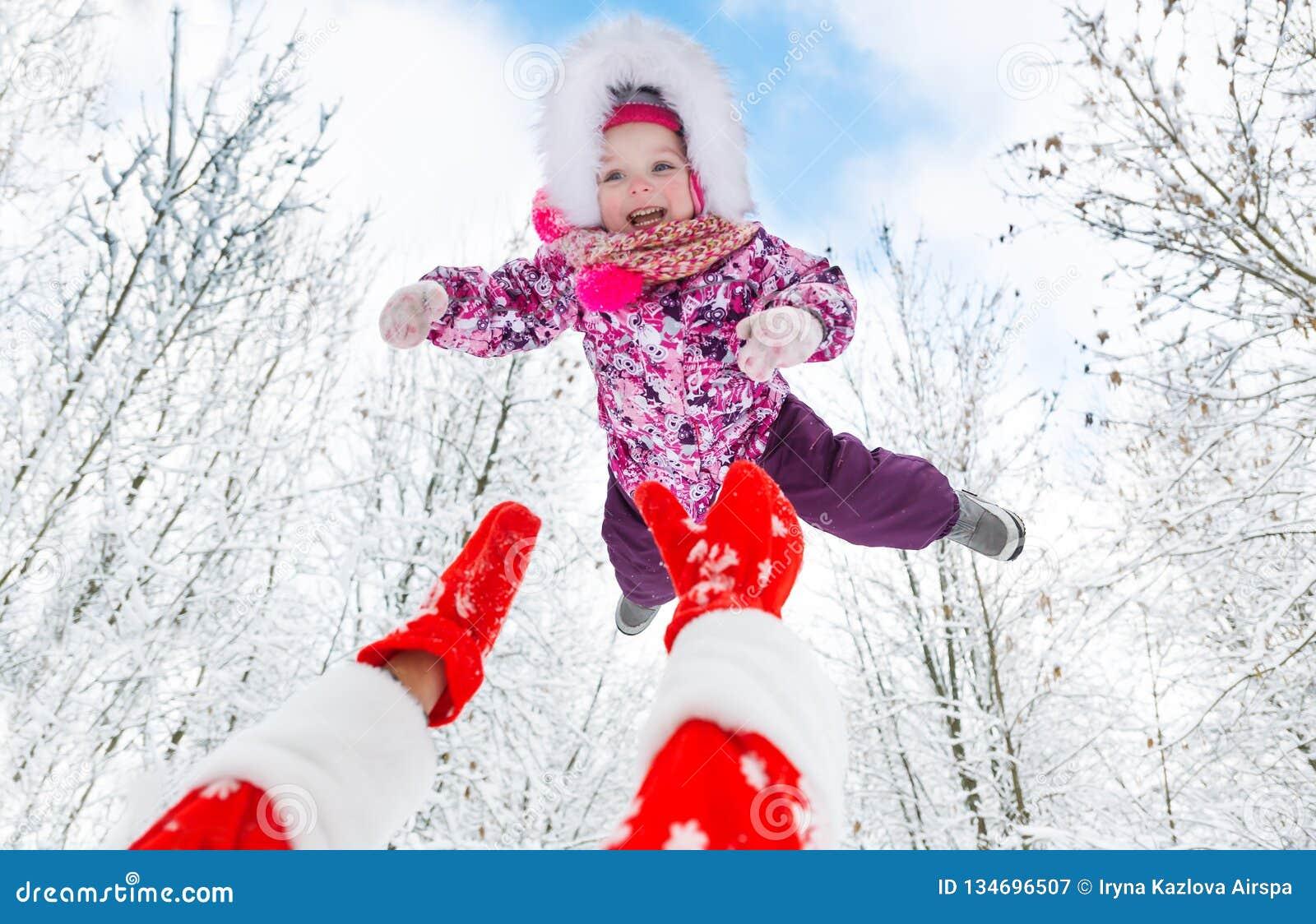 Santa Claus wirft oben obenliegendes nettes kleines Mädchen im Winterwald auf Weihnachten