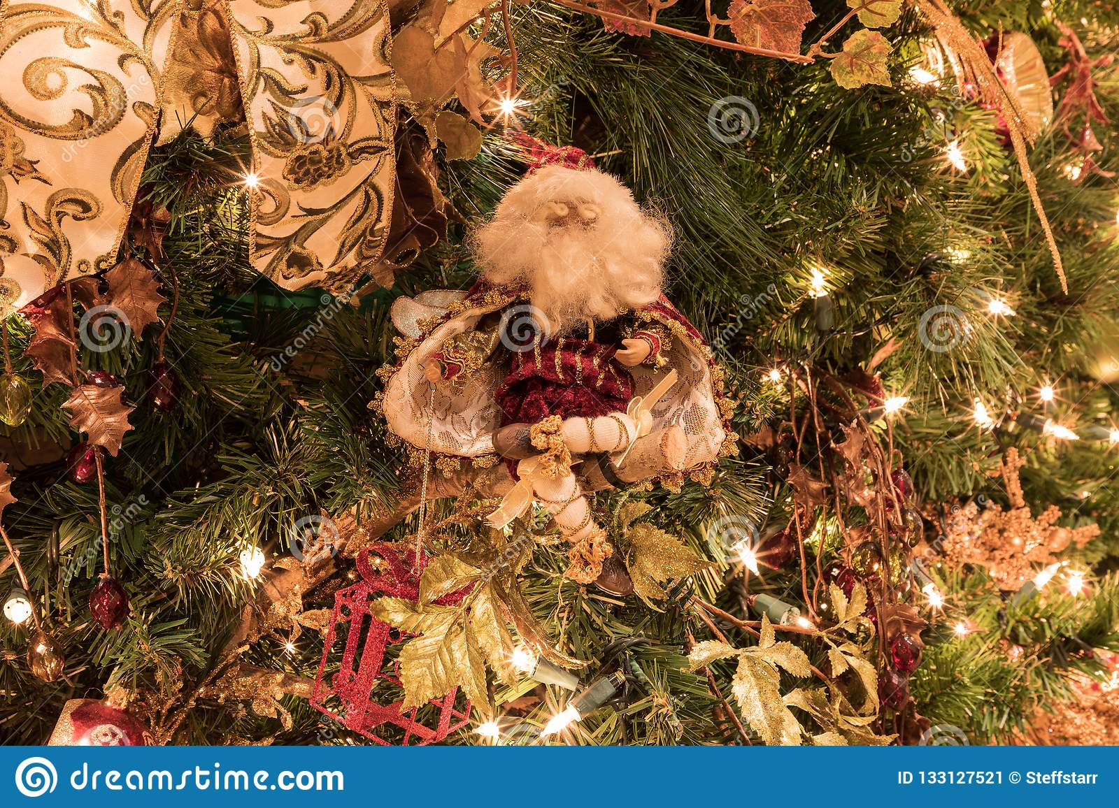 The Christmas Clause.Santa Clause Ornament On A Christmas Tree With White Lights