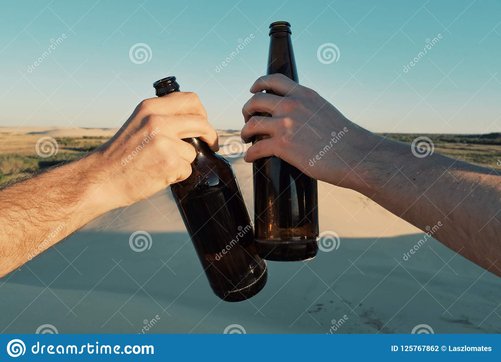 Two Young Man Clinking Beer Bottles Of Beer In The Desert