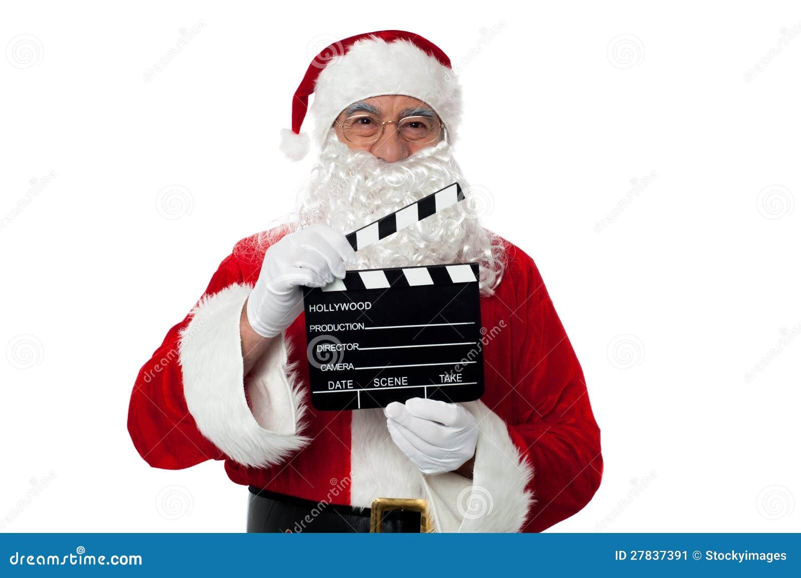 Santa envejecido alegre que presenta con un clapperboard